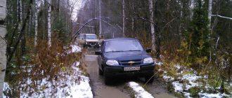 Нива Шеви на лесной дороге в снегу